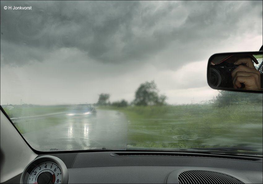 Een buitje onderweg, auto langs de kant bij regen, slagregen, korte heftige bui, rijden bij slecht weer, lichten aan bij slecht weer, fotograferen vanuit de auto, heftig weer, kooi van Faraday, slecht weer fotograferen
