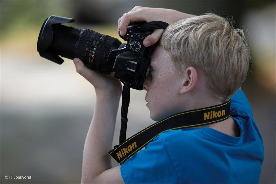 Een jeugdig talent, Jeugdige fotograaf, De kleine fotograaf, kijken door de zoeker, aandacht voor compositie, fotografie, Foto